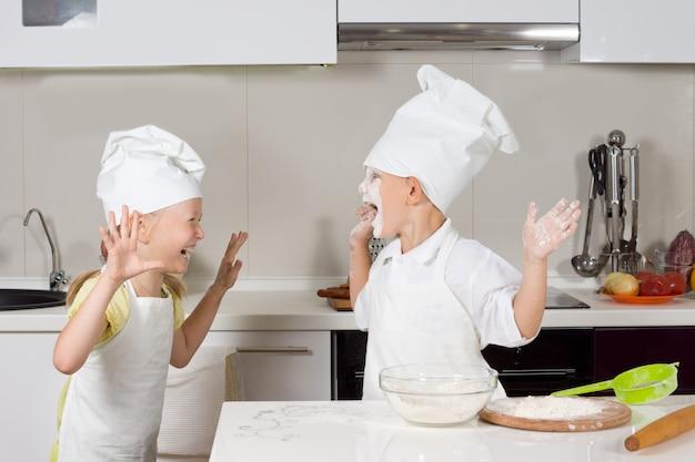 Zwei süße kinder, verkleidet als köche, spielen in der küche herum