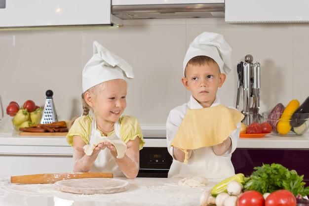 Zwei süße kinder zeigen teig, den sie in der küche gemacht haben.