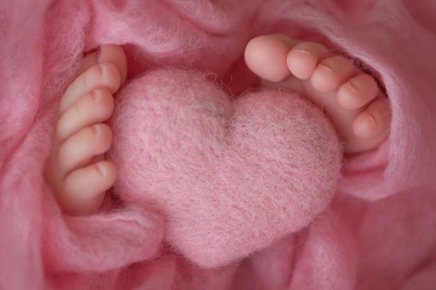 Zwei süße kleine babyfüße, eingewickelt in eine rosa strickdecke. und ein gestricktes herz aus wollfäden. foto in hoher qualität