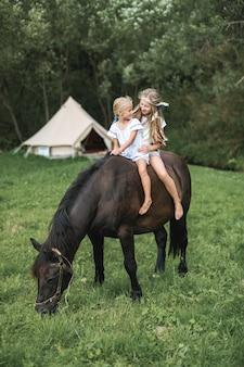 Zwei süße kleine blonde mädchen reiten ein braunes pferd, schauen sich an und haben spaß