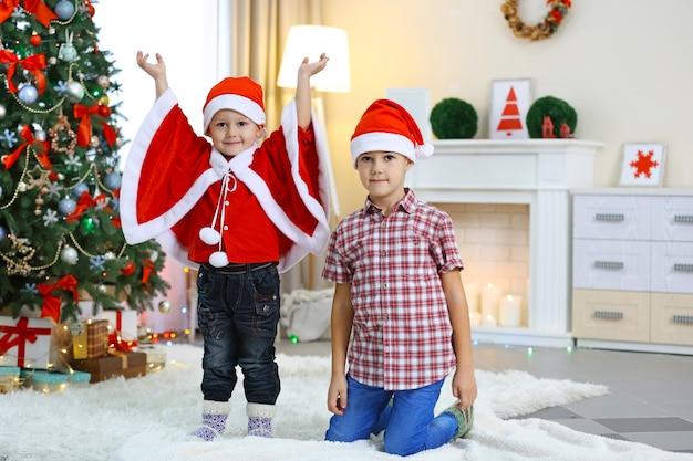 Zwei süße kleine brüder auf weihnachtsdekoration