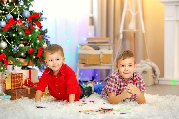 Zwei süße kleine brüder, die auf weihnachtsbaumhintergrund zeichnen
