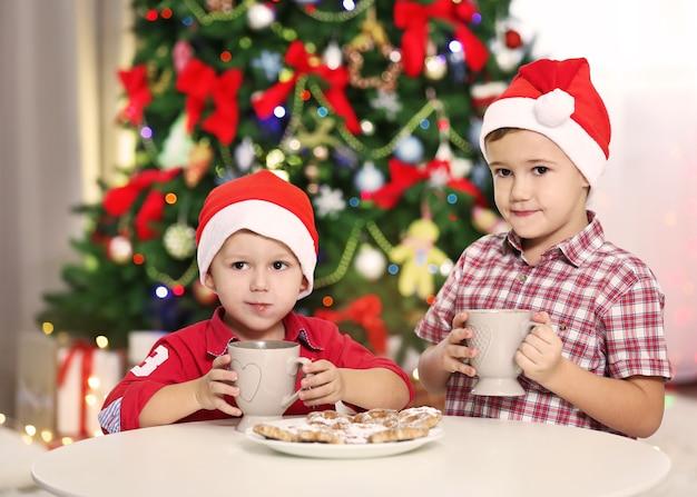 Zwei süße kleine brüder, die kekse auf weihnachtsdekorationshintergrund essen