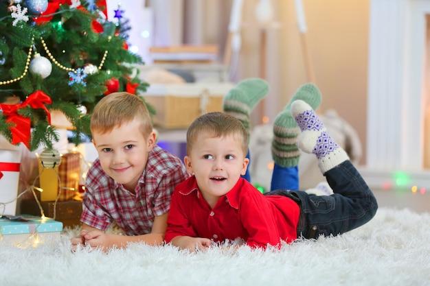 Zwei süße kleine brüder liegen auf dem teppich auf dem weihnachtsbaumhintergrund