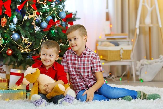 Zwei süße kleine brüder mit teddybär auf weihnachtsbaumhintergrund