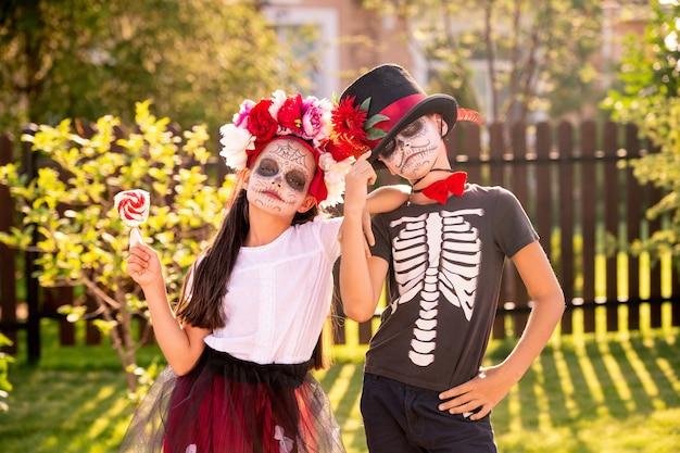Zwei süße kleine kinder mit gemalten gesichtern, die nahe beieinander vor der kamera stehen und sie betrachten, während sie halloween feiern