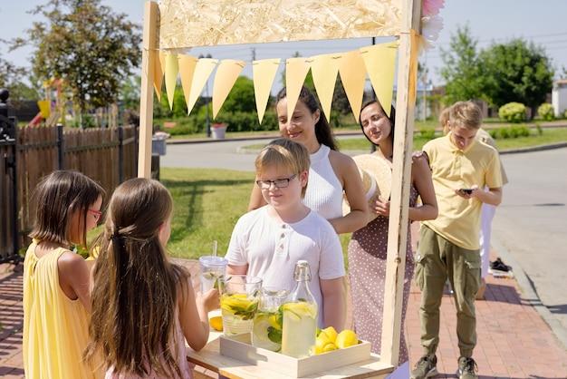 Zwei süße kleine mädchen, die an einem holzstand stehen und an einem heißen tag frische selbstgemachte limonade an durstige menschen verkaufen, die eine lange schlange bilden