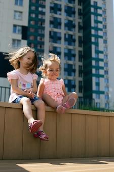 Zwei süße kleine mädchen, die draußen in der stadtlandschaft sitzen. generation alpha. hochformat, schwestern
