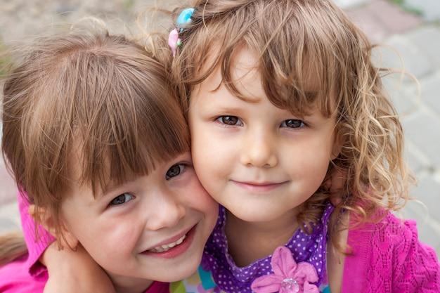 Zwei süße kleine mädchen, die zusammen umarmen