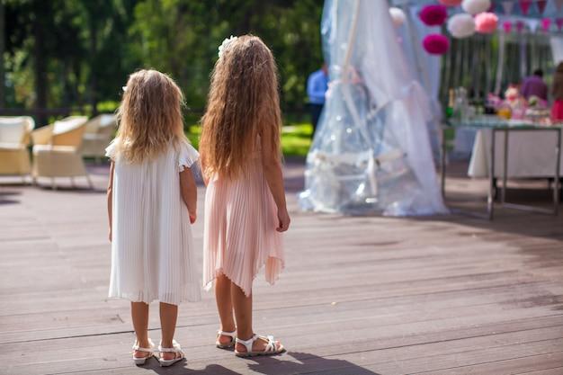 Zwei süße kleine mädchen in wunderschönen kleidern auf der hochzeitszeremonie
