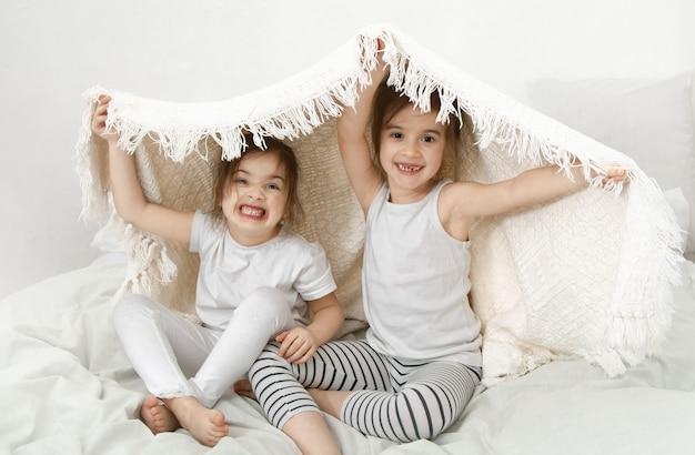 Zwei süße kleine schwestermädchen kuscheln auf dem bett im schlafzimmer.