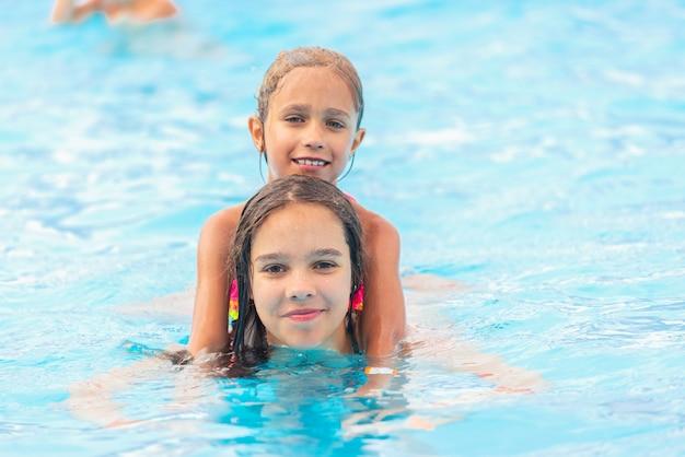 Zwei süße kleine schwesternmädchen schwimmen im pool
