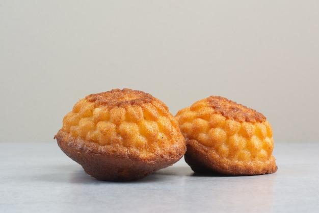 Zwei süße köstliche cupcakes auf weißem hintergrund