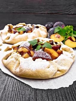 Zwei süße kuchen mit pflaume, zucker und kardamom auf pergament, minzzweige auf holzbretthintergrund