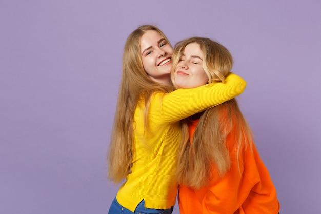 Zwei süße lächelnde junge blonde zwillingsschwestern mädchen in lebendigen bunten kleidern umarmen sich einzeln auf pastellvioletter blauer wand. menschen-familien-lifestyle-konzept.