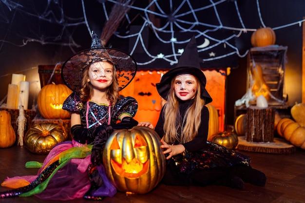 Zwei süße lustige schwestern feiern den feiertag. lustige kinder in karnevalskostümen bereit für halloween in halloween-dekorationen