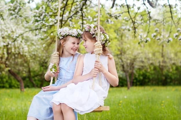 Zwei süße mädchen, die spaß auf einer schaukel im blühenden alten apfelbaumgarten haben. sonniger tag. frühlingsaktivitäten im freien für kinder