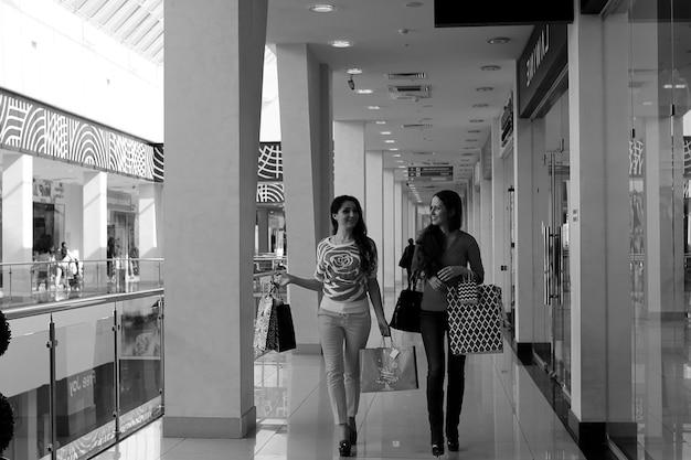 Zwei süße mädchen gehen im einkaufszentrum einkaufen