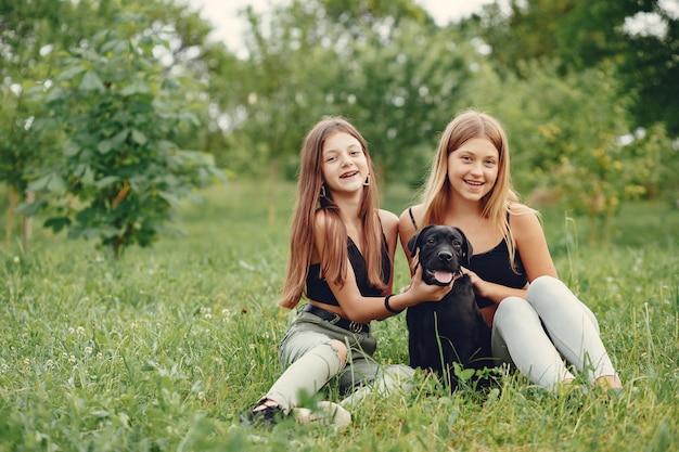 Zwei süße mädchen in einem sommerpark mit einem hund