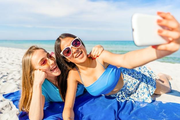 Zwei süße mädchen liegen auf weißem sand und machen ein selbstporträt mit handy mit lustiger sonnenbrille