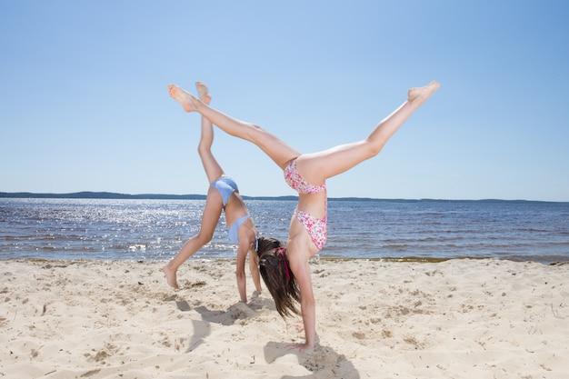 Zwei süße mädchen machen wagenrad am strand