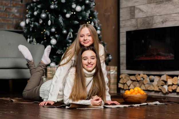 Zwei süße mädchen sitzen auf einem sofa in einem weihnachtsinnenraum mit einem weihnachtsbaum. neujahrskonzept