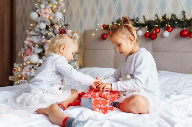 Zwei süße mädchenschwestern mit weihnachtsgeschenken sitzen zu hause im weihnachtlich dekorierten zimmer auf dem bett. glückliche kinder, heiligabend.