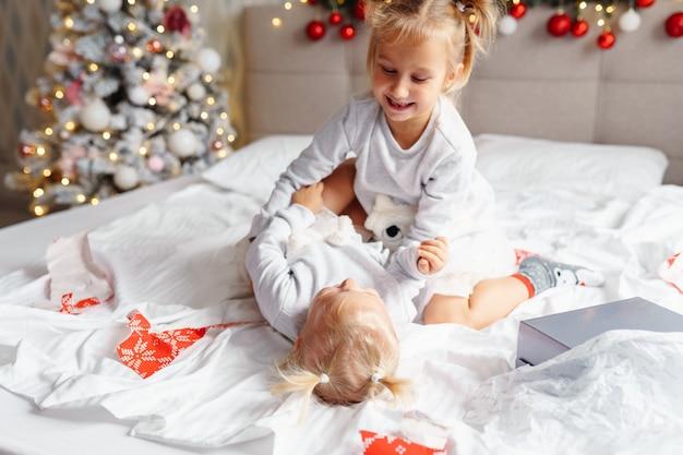 Zwei süße mädchenschwestern spielen zu hause im weihnachtlich dekorierten zimmer auf dem bett. glückliche kinder, heiligabend