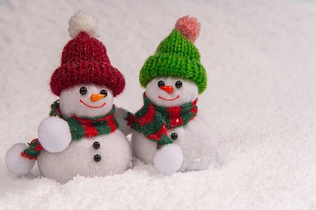 Zwei süße schneemänner stehen im schnee und lächeln