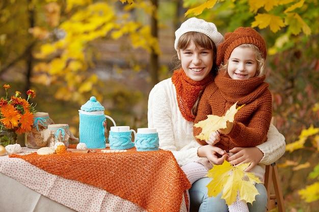 Zwei süße schwestern beim picknick im herbstpark.