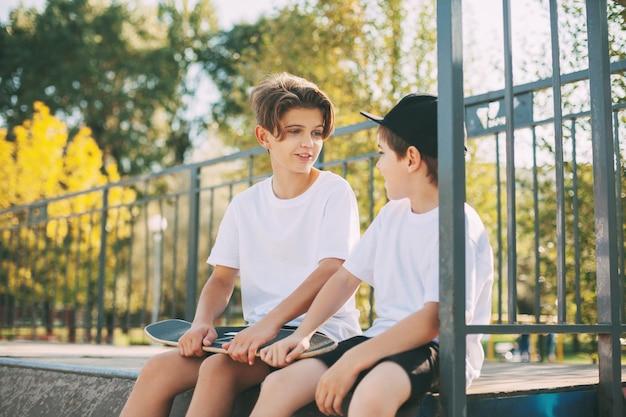 Zwei süße teenager sitzen in einem skatepark, entspannen sich nach dem skateboarden und unterhalten sich. das konzept der jugend