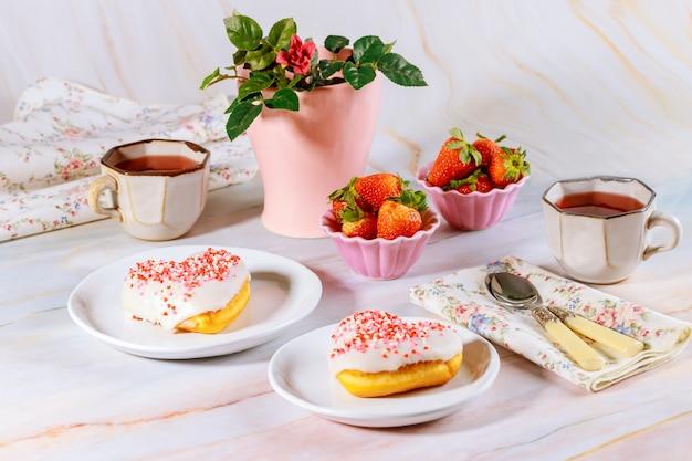 Zwei süße und rosa herzförmige donuts mit weißer glasur und streuseln auf dem partytisch mit tee, erdbeeren und rose.