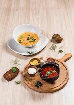 Zwei suppen in weißen und schwarzen schüsseln auf holztisch in einem restaurant. zutaten auf holz