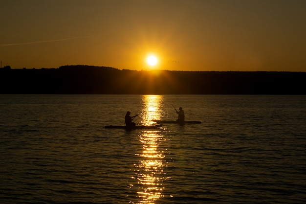 Zwei surfer sitzen und rudern auf standup-paddleboards vor dem hintergrund der untergehenden sonne