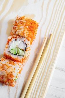 Zwei sushi-rollen mit garnelen- und gemüserogen-nahaufnahme. sushi mit stäbchen essen Premium Fotos