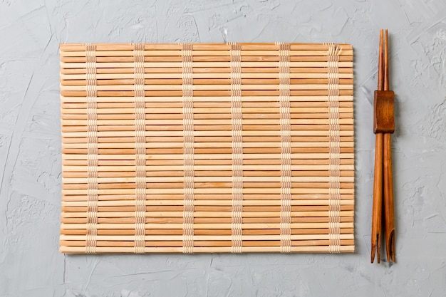 Zwei sushi-stäbchen mit leerer bambusmatte oder holzplatte