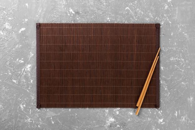 Zwei sushiessstäbchen leeren bambusmatte oder hölzerne platte auf draufsicht des zementes mit copyspace. leere asiatische küche hintergrund