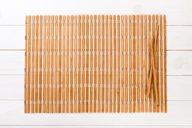 Zwei sushiessstäbchen mit bambusmatte für hintergrund