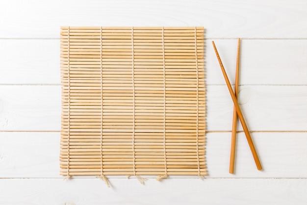 Zwei sushiessstäbchen mit leerer bambusmatte auf holz
