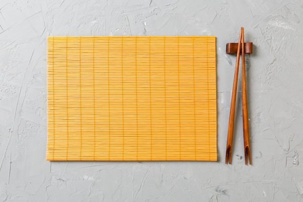 Zwei sushiessstäbchen mit leerer bambusmatte