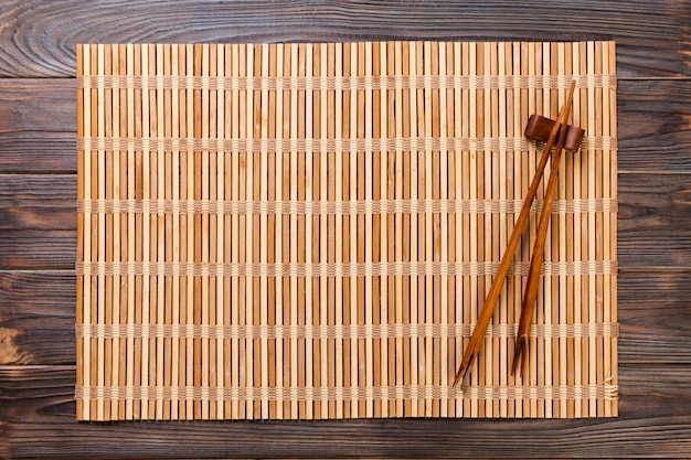 Zwei sushiessstäbchen mit leerer brauner bambusmatte oder hölzerner platte auf hölzernem