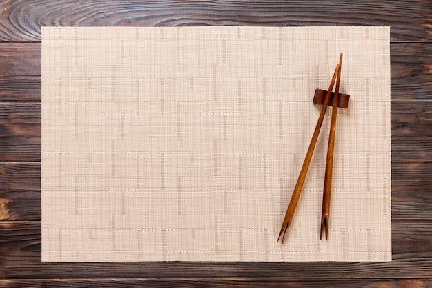 Zwei sushiessstäbchen mit leerer brauner bambusmatte oder hölzerner platte auf holz