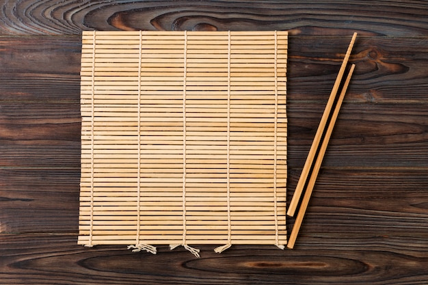 Zwei sushiessstäbchen mit leerer brauner bambusmatte