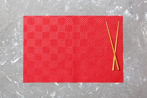 Zwei sushiessstäbchen mit leerer roter tischdecke, serviette auf draufsicht des zementes mit copyspace. leere asiatische küche hintergrund