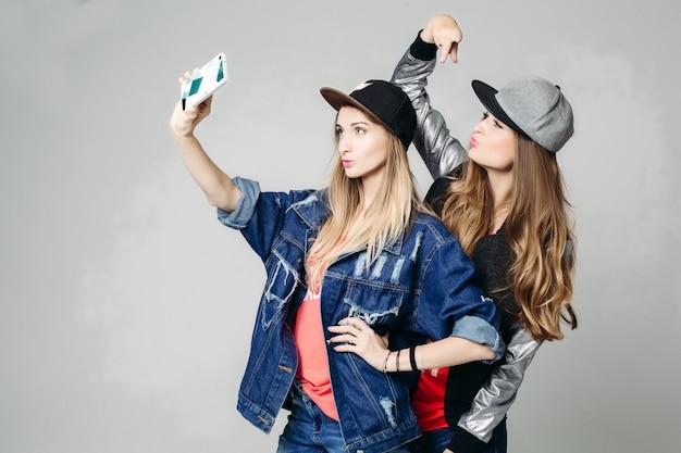 Zwei swagschwestern, die selbstporträt am anruftelefon nehmen.