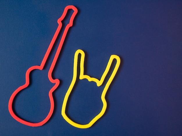 Zwei symbole der roten gitarre und der gelben heavy-metal-rock-teufelshörner geste auf blauem hintergrund
