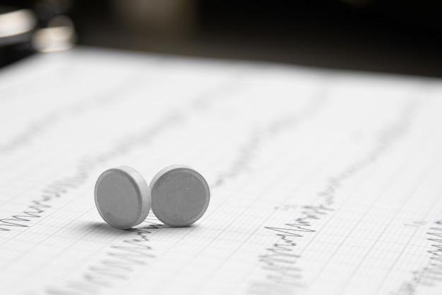 Zwei tabletten auf einem elektrokardiogrammblatt