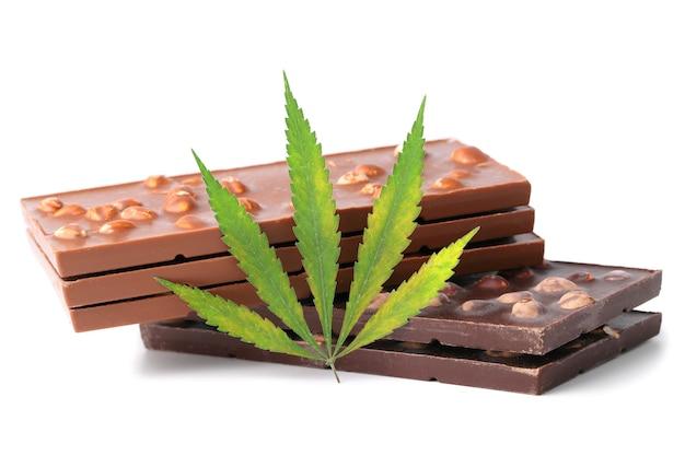 Zwei tafeln schwarze und drei milchschokolade und ein grünes hanfblatt