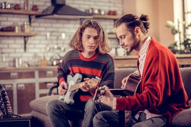 Zwei talentierte studenten verbringen ihr wochenende mit gitarrespielen