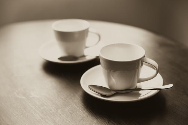 Zwei tasse kaffee auf hölzernem tabellensitzungskonzeptweinlesefarbton